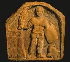 The tombstone of a murmillo gladiator, holding the palm of victory. His helmet lies beside him on the ground. (Alamy)
