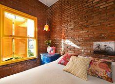 Para combinar com o clima praiano, um dos quartos tem parede com tijolos à mostra, no maior estilo rústico (Foto: Vanessa Bohn/Bohn Fotografias)