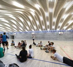 A sunken sports hall where an arching wooden roof doubles up as a hilly courtyard by Danish architecture studio BIG.