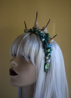 Heres a crown fit for a mermaid princess! It features seashells, abalone shell fragments, pearl beads, multi-faceted pave beads, gem beads, and other opalescent beads of various sizes on a wide plastic headband. This crown is in a green/blue/turquoise colorway. The photo of the mermaid shows her wearing a different crown, but it should give you an idea of how it will look on an actual person...like you! Convo me for overseas shipping or special orders.