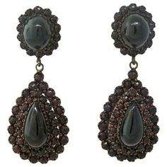 Antique earrings of gilt silver and low carat gold, set with bohemian garnets. DESIGNER: Not Signed MATERIAL: Low Carat Gold GEMSTONE: Garnet DIMENSIONS: Earrings measure 53mm x 20mm WEIGHT: 17.9g MAR