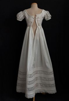 The endearing simplicity of the hand sewn dress commands our admiration because of the skillful adaptation of the Neoclassical style. Due to its association with classical antiquity, the white gown embodied the Neoclassical ideal. The simple white cotton dress symbolized a romanticized pastoral life, celebrated by classical writers as well as by their Neoclassical imitators.