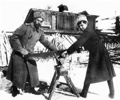 Czar Nicholas II, left, and his son Prince Alexei sawing wood to heat the dwelling in Siberia where they were held prisoner in 1918. They and the rest of the Russian royal family were executed in July 1918, and their remains were covered up for decades.