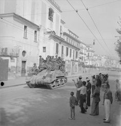 A Sherman tank loaded with infantry is cheered by local people as it passes through Salerno, 10 September 1943.