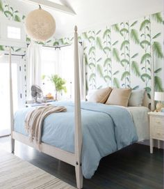 In this California home, the owner's inspired use of wallpaper augments the endless-summer fantasy, like this Cole & Sons design that evokes palm trees in the master bedroom. An Ethan Allen four-poster and a Horchow capiz-shell pendant imbue the room with a vacation-villa vibe. The Belgian linen duvet cover is by Restoration Hardware.