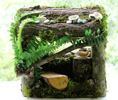 Moss, ferns, bark and branches make up the structure but you also get a bench or settee with a side table. On the outside is a bird house tucked into the crest of the house and on the other side is moss and bark. You also find a wicker awning. There are stones, shells, pebbles, lichen and clear globes for the fairies to light with their magic.