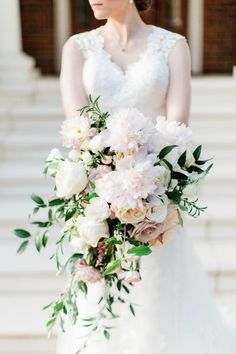Stunning blush peonies, cream and Quicksand roses, Italian Ruscus and dark foliage cascade bouquet by Bella Rose Floral & Design | Preston & Christina at Bella Rose Plantation in Lynchburg, VA - an Entwined Events venue | Natural Elegance & Unwavering Love – The Forever Entwined Blog | Amanda Somerville Photography