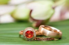 Orange sapphire rose gold engagement ring with diamond halo and textured sides. Matching orange sapphire wedding band with elegant engraving. Wedding rose gold ring with satin finish. The set is made by our own Gary Shteyman.