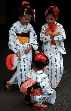 Japanese girls in yukata: yukata    comfortable cotton kimono decorated with stencil-dyed patterns usually in shades of indigo, worn by Japanese men and women. The yukata was originally designed as a nightgown and for wear in the home after a bath.