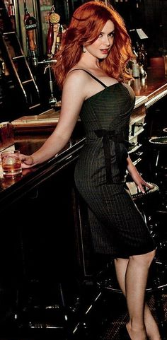 Christina Hendricks in black dress in a bar ...a whiskey and a curvey redhead...what more could any man want...