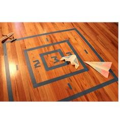Paper Airplane Target Craft--put this together tonight & instead of taping an outline on the floor, I drew a target on the back of the carpet in the play room.