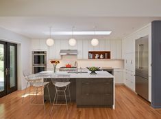 mid century kitchen clean white and flat panel kitchen cabinets stainless steel appliances white top kitchen island with dark wood cabinets medium toned wood planks floors modern white bar stools of Tens of Inspiring Kitchen Islands with Storage and Chairs