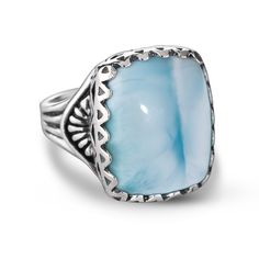 This unique and beautiful ring is a statement piece for your fingers! A substantial cushion cut cabochon of larimar sits atop stamped sterling silver in western motifs. The beautiful sea color of this stone will make you wish you were sitting pool side on a hot summer day - maybe you should be! Expect compliments when you wear this fabulous piece.