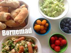 Børnemad. Aftensmad bestående af små pølsehorn med sesam, tomater, blåbær og en simpel pastaret med ærter og pølser.