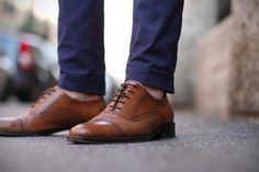 Going sockless looks best with well-fitted, tapered pants with minimal to no break.  Wearing baggy pants that puddle at your shoes not only looks bad in general, it defeats the purpose of going sockless.