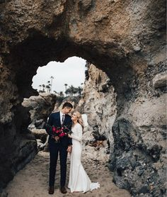 Beautiful, elegant, modern beach wedding pictures on sand with rocky arch and palm trees.