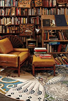 Lush bohemian library! Love the vintage tan leather arm chair, boho rug and masses of books.