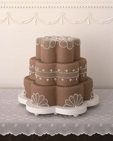 For as long as brides have dreamed of multitier wedding cakes, they have envisioned icing swirls and swags adorning them. Today's bakers (and brides) continue to make wonderful use of traditional piping techniques. As these creations show, designs can be fresh and unique. Ask to see samples of a baker's work, either photographs or prop cakes on display in the shop, before commissioning him or her to render your vision in icing. You'll generally pay more for a cake with intricate piping; such…