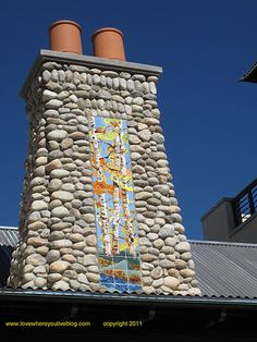 Tile mural decorates chimney covered in river rock, complements terra cotta chimney pots.
