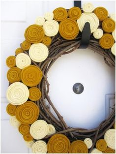 Terrific wreath. Flowers made from strips of wool felt. Clever lady!
