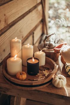 An autumnal picture of candles, squashes and steaming kettles.