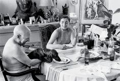 Jacqueline and Pablo Picasso sitting at the dinner table. Picasso is holding a dachshund in his lap. The dog is licking a dinner plate. Pablo Picasso, Picasso Dachshund, Dachshund Love, Guernica, Warhol, T Magazine, Life Magazine, Spanish Painters, History Of Photography
