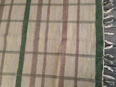 Cottage chic green, beige and brown woven rag rug. In sporadic placement are cloth strips of soft yellow giving the rug a warm feel.33 inch…