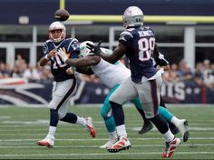 New England Patriots quarterback Jimmy Garoppolo (10) flips a pass to Martellus Bennett (88) while in the grasp of Miami Dolphins defensive tackle Jordan Phillips (97) during the first half of an NFL football game Sunday, Sept. 18, 2016, in Foxborough, Mass.