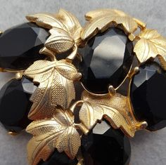 This vintage Schiaparelli brooch is a dramatic display with midnight black rhinestones and gold plated leaves. Stunning and sophisticated. It is 2-1/4