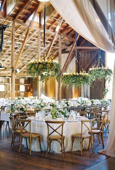 If you're marrying indoors, help bring the outdoors in by decorating the light fixtures with pretty greenery, like these lush hops vines.