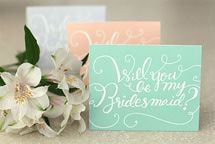Green, coral, and white Will You Be My Bridesmaid? cards on a table. - © Something Pretty