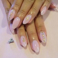 Beautiful almond shaped nails with a soft sheer pink polish and a few gold jewels for accent.