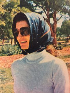 Jackie Kennedy in turtleneck and head scarf.