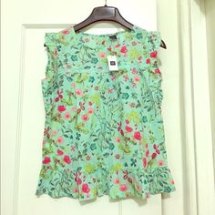 Floral lace trim flutter top. Smooth cotton weave with picot flutter sleeves & ruffle hem. Lace trim & shirting at front yoke. Rear button & loop closure. In a shore blue flowered cotton fabric. Kids XXL, fits up to a womens large. GAP Tops Tank Tops