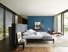 La cama, el vestidor y las mesas auxiliares de la habitación principal son de #RocheBobois; la silla Eames y el otomano de #HermanMiller, las lámparas a los lados de la cama pertenecen a #FontanaArte, y la pared está pintada en el tono Patagonia de #Comex.
