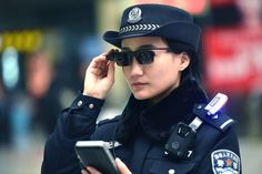 A policewoman uses facial-recognition sunglasses while patrolling a train station in Zhengzhou, the capital of...