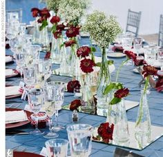 The Centerpieces  A row of square mirrors topped with baby's breath and zinnias highlighted the length of each banquet-style table. Blue, pintuck linens worked in the other color in the scheme, while photos of the couple's cats served as the backdrop for the table numbers.
