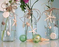 Vasos de vidro enfeitados com conchas do mar