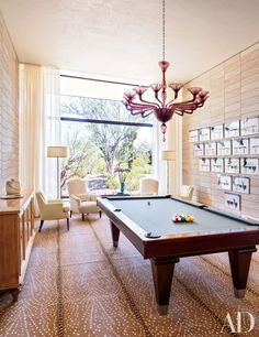 In the game room of an Arizona home by Jan Showers, a Blatt Billiards table is set on a Stark carpet beneath a vintage Murano-glass chandelier; the multipart artwork is by Robin Rhode.