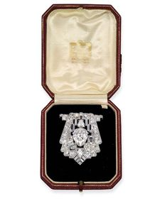 An Art Deco Diamond Brooch by Cartier. The shield-shaped brooch set with a pear-shaped diamond weighing 7.74 carats within a pavé-set diamond openwork surround with baguette-cut and pear-shaped diamond detail, circa 1925, 4.5 cm long, in fitted red leather Cartier case. Signed Cartier, London.