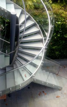 Custom Staircase | Floating  | Exterior | #BlankandCables In order to create this apparently seamless glass and steel staircase, Blank and Cables welded and assembled the stainless steel and stone on-site to create the stair's skeleton. Afterwards, the glass was installed with such a high level of precision that it appears to be one continuous sheet wrapping around the spiral stair. The clean and modern design is a creative solution that provides a roomier aesthetic.