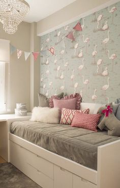 deco petite chambre adulte avec des flamingos roses sur le mur, lit blanc avec des grands tiroirs blancs, matelas du lit gris et des coussins blancs, roses et fuchsia, lustre avec des pampilles de cristal #decoracionniñashabitacion