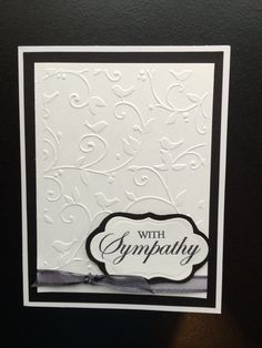 "Sympathy card using Spellbinders Petite Labels One Die D-Lites and ""With Sympathy""clear stamp. 5x6.5"" pre-made white card was layered with black card stock and white card stock embossed with Cuttlebug - Birds and Swirls embossing folder. Black sheer ribbon was used behind the label and tucked under the white card stock layer. Created by: Melanie Weise"