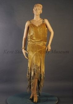 1927-29 Sandy gold panne velvet evening dress. Dress with V neck and heavily beaded straps, dropped waist with horizontal panel gathered at front and sides to appear as belt, bias cut skirt with irregular pointed hem, longer in back, with band of chiffon and large flowers of velvet and chiffon with pearls and diamonds.