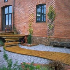 Decking in the form of a curving path appears to flow through a pea gravel base like a stream (House to Home).