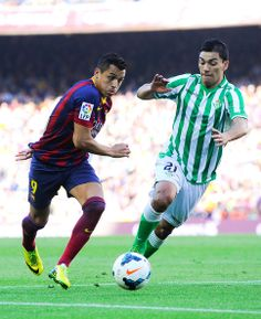 Alexis Sanchez (L) of FC Barcelona duels for the ball with Lorenzo Reyes of Real Betis Balompie during the La Liga match between FC Barcelona and Real Betis Balompie at Camp Nou on April 5, 2014 in Barcelona, Catalonia.