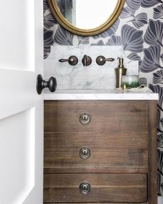 Perfect powder room with patterned wall paper.