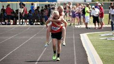 Twin carries sister over finishing line in Southern Illinois state track meet.