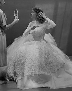 An all important last minute check. 1950s wedding dress. Love the calm, relaxed pose of the bride