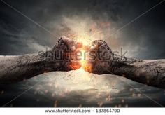 Fight, close up of two fists hitting each other over dark, dramatic sky - Shutterstock Premier